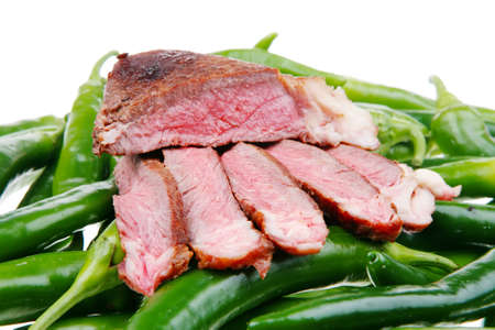 meaty: meaty food : roasted red meat steak sliced on a green hot chili peppers on a white back