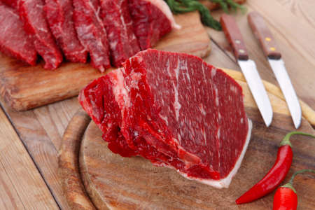 knives: fresh raw beef meat steak and chunk with red hot pepper and dill on wooden cut plates over table Stock Photo