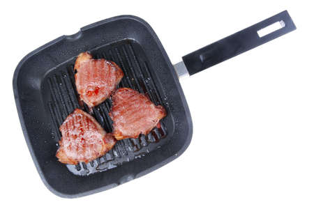 teflon: roast bloody beef fillet steaks on black teflon grill plate isolated on white background
