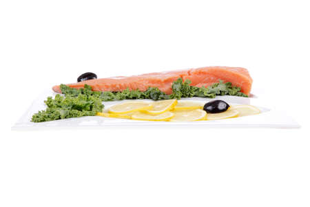 fish plate: healthy food - fresh raw red fish with kale lemon and black olives on plate isolated on white background space for text