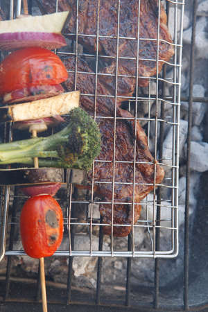 barbequing: fresh beef steak fillet mignon on meat holder over charcoal grid with vegetable shish kebab tomato broccoli,red onion on skewer ready to prepare for outdoor party Stock Photo