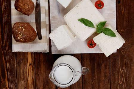 latte fresco: latticini freschi bianco greco ovino caprino feta sulla piastra con il latte in brocca ciliegia pomodori panino francese sulla tavola di legno scuro