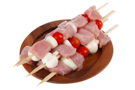 kebab: fresh raw meat fillet shish kebab turkey pork pink on skewers tomatoes mushrooms on wooden dish isolated over white background