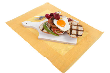 junk: junk food meat big beef hamburger fried eggs on white wood plate with cutlery ketchup sauce and pickels on yellow mat isolated over white background