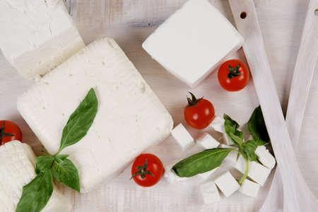 cabra: alimentos lácteos frescos blanco griego ovejas cabra queso feta en el plato con la leche en jarra tomates de cereza bollo de francés sobre la mesa de madera oscura Foto de archivo