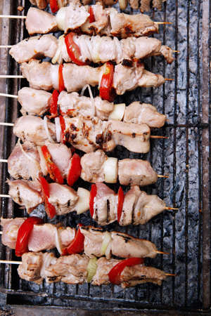 kabab: fresh turkey pink brisket shish kebab on wooden skewers with tomatoes over barbecue brazier full burned charcoal