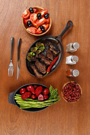 carne alla griglia: lunch of grilled meat served on black iron pan with asparagus pickles tomatoes olives hot black red pepper salt on wooden table