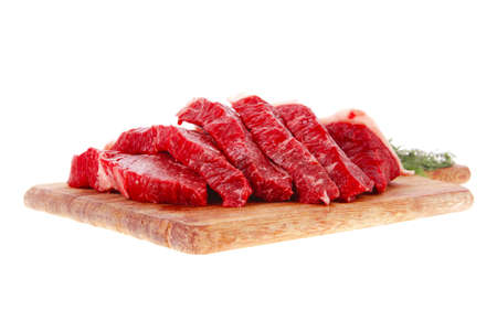 carne cruda: frescas rebanadas de carne de vacuno de carne cruda en la tabla de corte de madera aislada sobre fondo blanco
