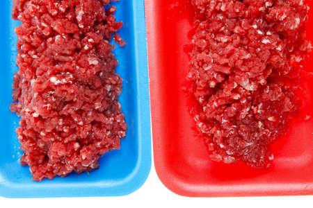 carne picada: carne de ternera picada cruda fresca en bandeja de rojo y azul sobre fondo blanco aisladas Foto de archivo