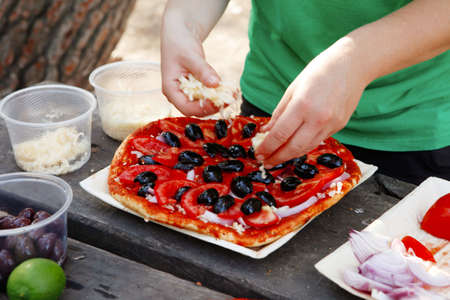make a paste: making hand made pizza with olives and tomatoes on wooden table on picnic Stock Photo