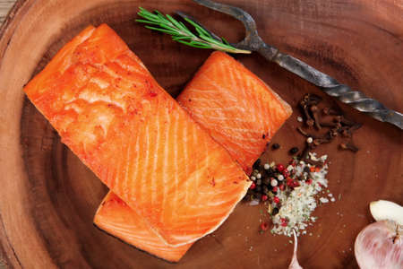 fresh: breakfast delicious portion of fresh roast salmon fillet with dry spices garlic and rosemary on wooden plate with black forged handmade fork healthy food diet cooking concept Stock Photo