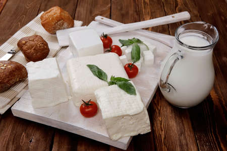 queso fresco blanco: dairy food fresh white greek goat sheep feta cheese on plate with milk in pitcher cherry tomatoes french bun over dark wooden table
