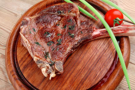 main course: served main course: grilled pork ribs served with green chives and cherry tomato on wooden plate Stock Photo
