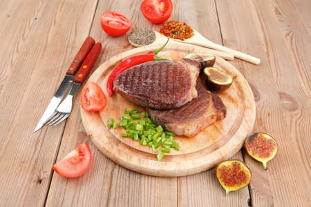 green stuff: meat savory : grilled beefsteak served with hot cayenne peppers green stuff sweet figs and cutlery on wood plate over wooden table