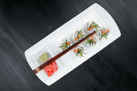 soysauce: Japanese Cuisine - California Roll made of Salmon, Cream Cheese and Avocado inside. Served with wasabi and ginger . on long white plate over black table