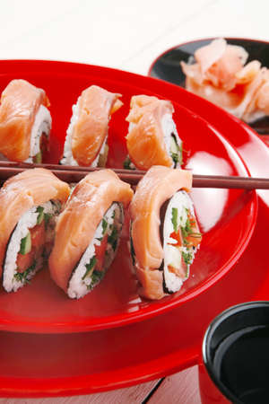 inside out: japanese cuisine onigiri sashimi inside out sushi rolls with ginger and sake cup on red plate over white wooden table