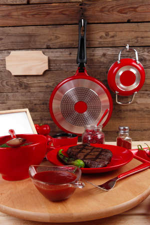nameplate: red theme lunch : fresh grilled bbq roast beef steak on red plate with green chili tomato soup ketchup sauce paprika small jug glass ground pepper american peppercorn and modern cutlery served on wooden plate over table empty nameplate menu board Stock Photo