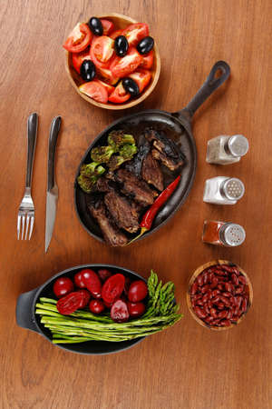 red hot iron: lunch of grilled meat served on black iron pan with asparagus pickles tomatoes olives hot black red pepper salt on wooden table