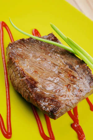 lean over: meat food : roasted fillet mignon on green plate with chives and ketchup over wooden table Stock Photo