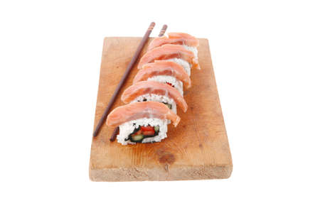 inside out: classic onigiri inside out californian sushi rolls with salmon on wooden plate isolated over white background with sticks Stock Photo