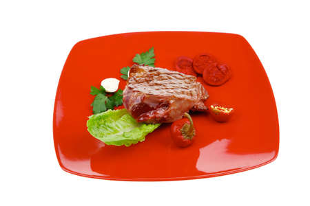 mouthful: bbq : beef (pork) steak garnished with green lettuce and red chili hot pepper on red plate isolated over white background