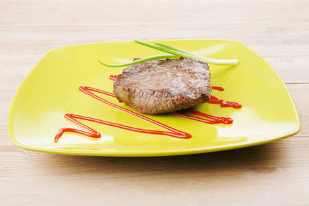 lean over: meat food : roast beef fillet mignon served on green plate with chives and ketchup over wooden table Stock Photo