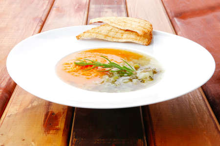 european cuisine: european cuisine: vegetable soup served with toasts on white dish on wooden table Stock Photo