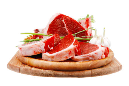 green stuff: fresh meat : raw uncooked fat lamb pork rib and fillet with green stuff and red chili pepper on wooden plate isolated over white background