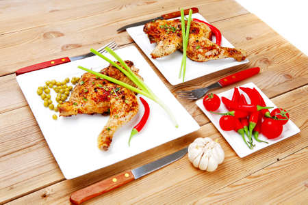 garnished: meat food : chicken legs garnished with green peas and and cutlery on white plates over wooden table Stock Photo