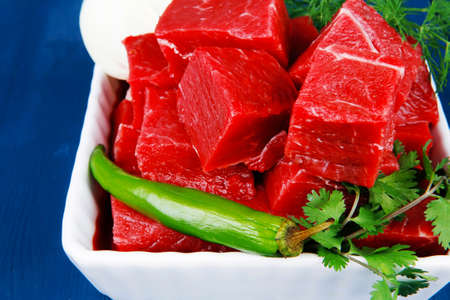 circular muscle: fresh uncooked beef meat slices over white bowls ready to prepare with green hot peppers and greenery serving over blue wooden table Stock Photo