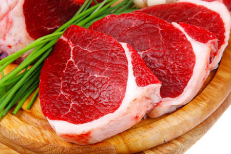 green stuff: butchery : fresh raw beef lamb big rib and fillet ready to cooking with green stuff on wooden plate isolated over white background