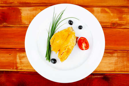 fryed: roasted fish fillet with tomatoes,chives and bread on plate over wooden table
