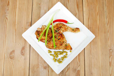 quarters: meat : chicken quarters garnished with green sweet peas and red hot pepper on white plate over wooden table