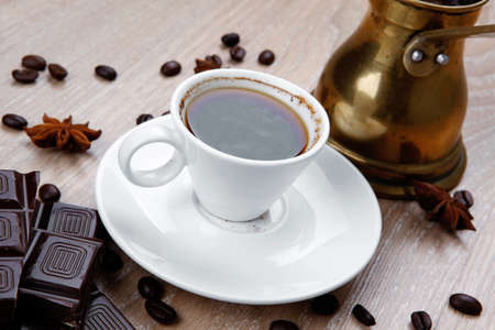 cezve: sweet hot drink : black Turkish coffee in small white mug with coffee beans spilled on a wooden table with stripes of dark chocolate and copper Arab Cezve full coffee