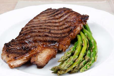 mesa de la carne: filete de carne a la parrilla con espárragos servido en un plato blanco con cubiertos sobre la mesa de madera Foto de archivo