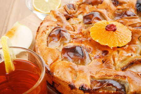 big apple: baked food : big apple pie served with fresh apples, raw lemon and mandarin,  tea cup on wooden plate over table