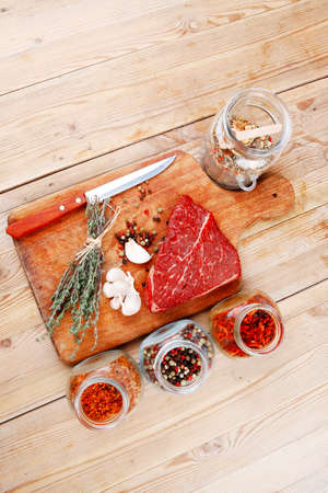 differnt: raw beef meat fillet with peppercorn and thyme and differnt spices in glass bottles ready to grill on wood figured aged board over table