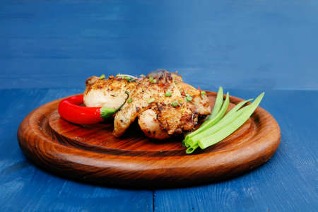 fine legs: roast meat : chicken legs garnished with green onion pens and peppers on wooden plate over blue wooden background