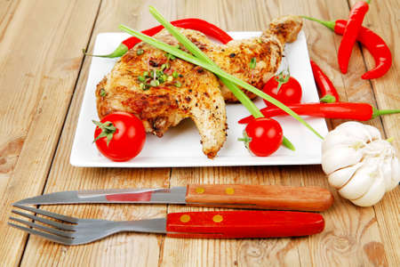 fine legs: grilled meat : grilled quarter chicken garnished with red peppers on white plates over wooden table Stock Photo