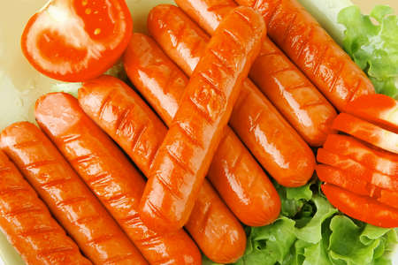 lean over: grilled sausages served on green dish wtih salad and tomato Stock Photo