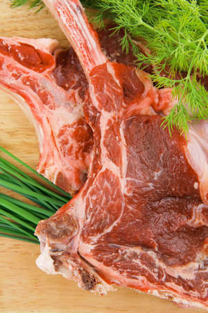 boned: raw meat : boned fresh ribs served with dill and green chives on wooden board isolated over white background