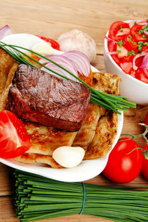 side of beef: grilled meat : beef ( pork ) garnished with tomatoes salad in bowl , green chives , and tomatoes on side on wooden table