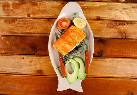 poisson servi: poisson saumon rôti sur une plaque de verre sur bois Banque d'images