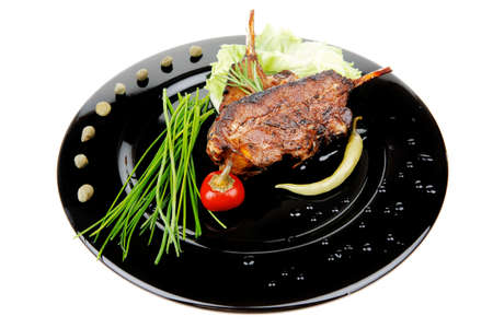 cooked pepper ball: savory plate: grilled ribs over black with peppers and green salad Stock Photo