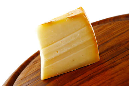 edam: piece of light edam cheese on wooden board