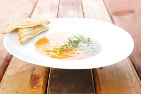 european cuisine: european cuisine: vegetable soup with toasts on white dish over wooden table Stock Photo