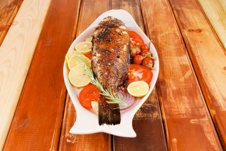 main course: main course: whole fried seabass served on wood with lemons,tomatoes and peppers