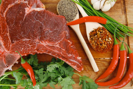 green stuff: fresh meat : raw uncooked fat lamb pork rib with green stuff and red chili pepper on wooden plate isolated over white background