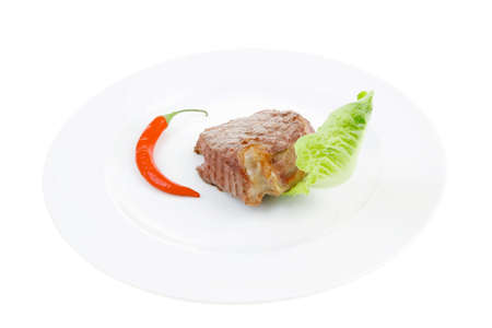 meat savory : beef fillet mignon grilled and garnished with green lettuce and red chili hot pepper on white plate isolated over white background
