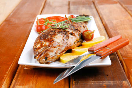 fryed: main course on wood: whole fryed sunfish on plate with lemons and peppers